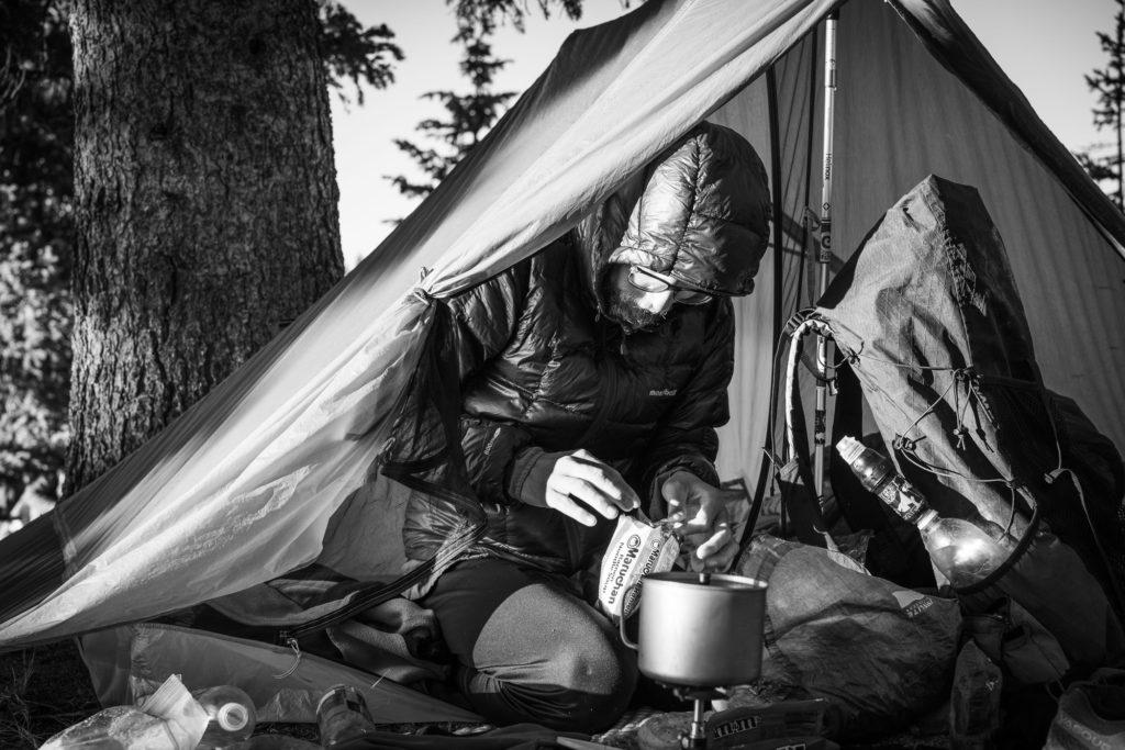 man making dinner inside his tent