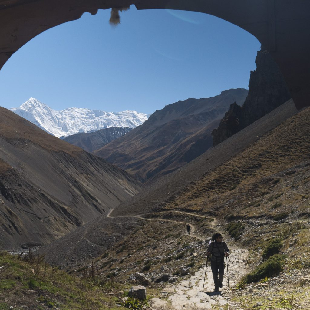 hiker passing through an archway with mountains in the background