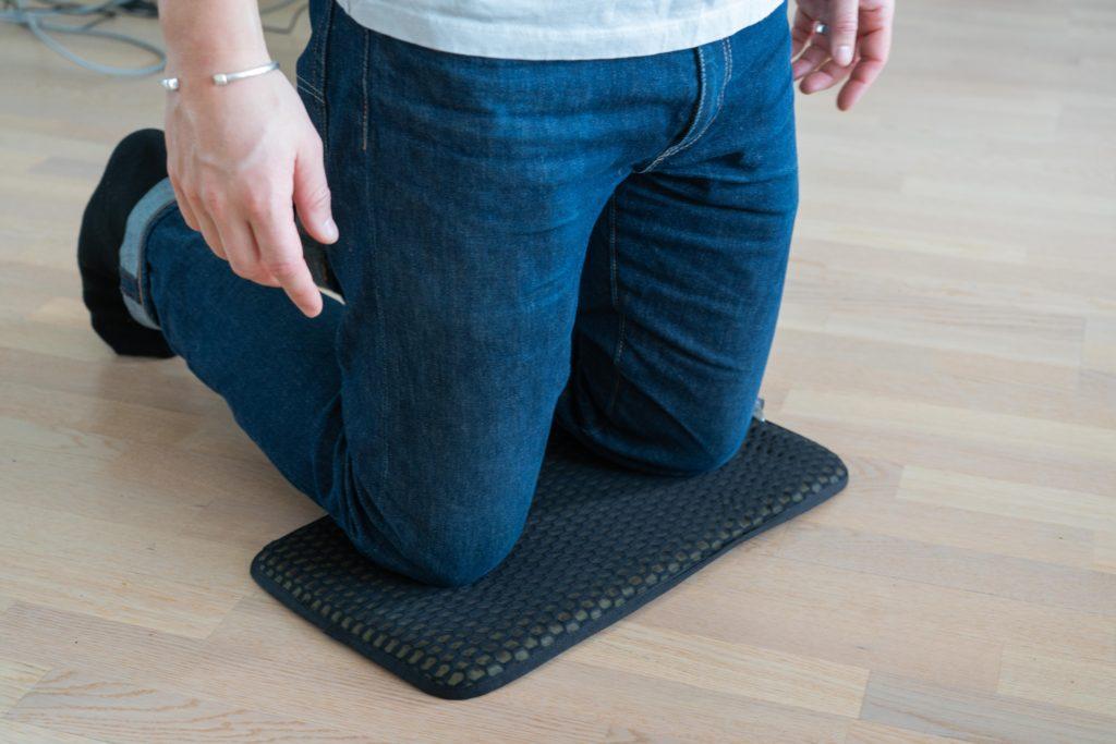 man kneeling on a sit pad