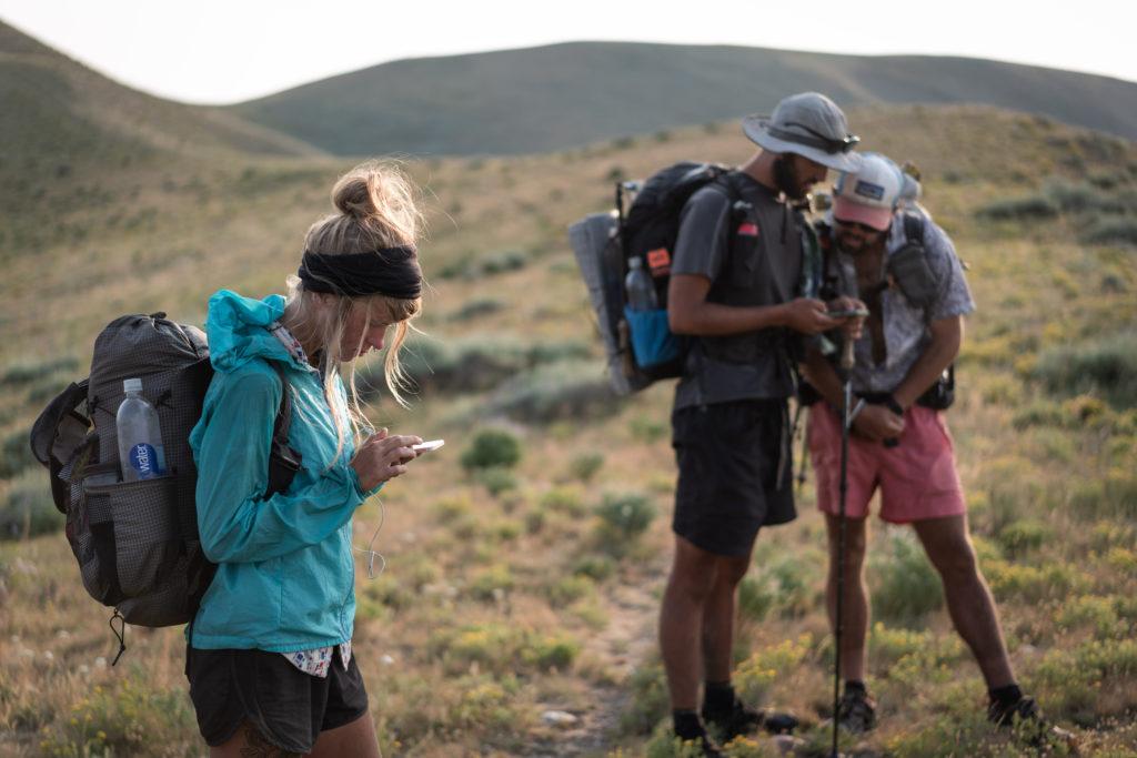 hikers on their phones